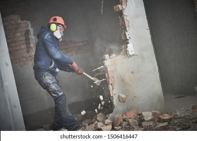 demolition work and rearrangement. worker with sledgehammer destroying wall