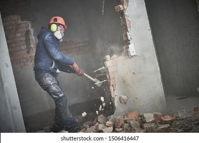 demolición y reorganización. obrero con martillo que destruye la pared