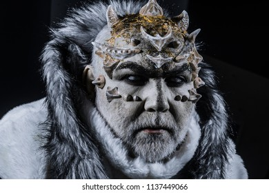 Demon with horns on head and shinning golden skin wearing white fur coat isolated on black background. Evil winter deity causing permafrost and death.