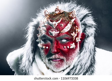 Demon with red face, harp thorns and white fur over dark background. Mystical enchanted creature living in perpetual cold. Guardian of permafrost land, fairy tale concept.