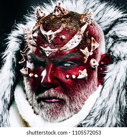 Demon with red face, sharp thorns and white fur over dark background, Halloween makeup idea. Mystical enchanted creature living in perpetual cold. Guardian of permafrost land, fairy tale concept.