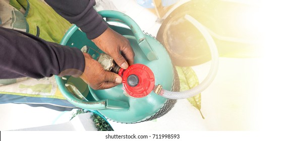 Demon shot service man to showing how to change Gas LPG tank 15 kilogram, At his hand is valve to disassemble to separate.