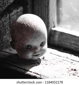 Demonic damned head of a doll in the dark room look at you.