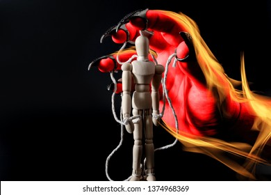 Demonic possession, black magic and a soul possessed by Satan concept theme with a puppet representing the human spirit controlled by the burning hand of demon or devil isolated on black background