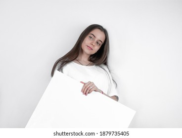 Demonstrating a blank sheet of paper, a beautiful woman attracts the eye.