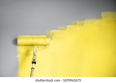 Demonstrating trendy Color of the Year 2021. Illuminating Yellow and Ultimate Gray. Brush and open paint can with on color background. Appartment renovation, repair, building and home design concept.