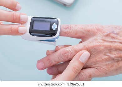 Demonstration of finger pulse oximeter. Close-up of women hands. Unrecognizable. From above