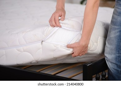 Demonstration of quality. A young man holding demonstrations quality mattress in the bedroom