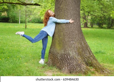 Demonstrative young woman hugging a tree standing on tiptoe in her enthusiasm in a lush green spring park