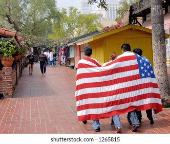 Demonstrators at Los Angeles illegal emigrant rally with US Flag. Olvera Street. May 1st 2006