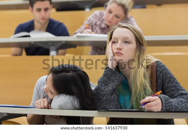 Демотивированные студенты сидят в лекционном зале с одной девушкой спала в колледже