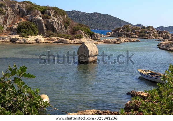 DEMRE, ANTALYA - JULY 18, 2015 : Seascape of Kekova Ancient Lycian City in Antalya, with a big sarcophagus in the sea, on bright blue sky background.