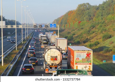 DEN DOLDER, UTRECHT, NETHERLANDS - October 16, 2019. Private cars and truck trailers with pallet transport are driving slowly at daylight on busy highway A28, stack in traffic jam. Speed limit 50 km.