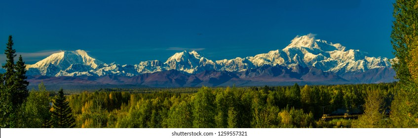 Denali, Mt Hunter and Mt Foraker in the alaska range, and the Alaska railway train.    Denali is the highest mountain peak in North America, with a summit elevation of 20,310 feet