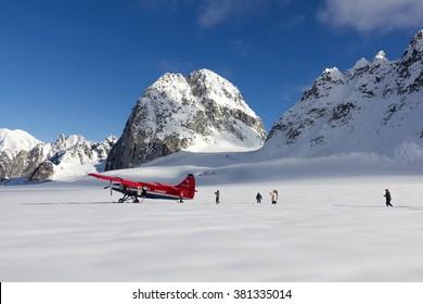 DENALI NATIONAL PARK, ALASKA, USA - SEPTEMBER 14, 2013: Tourists walking in deep snow after plane landing on Pika Glacier near Mount McKinley.