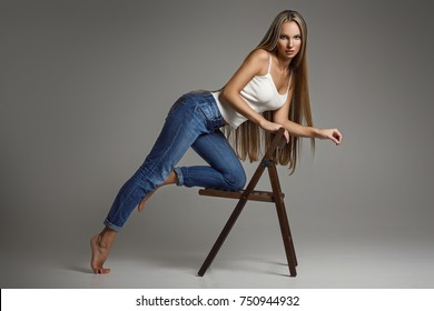 Denim beauty. Studio shot of beautiful young woman in jeans overall looking at camera while sitting on the chair