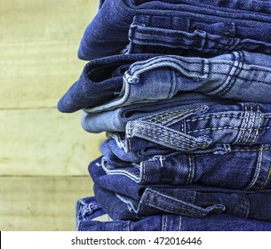 denim fashionable clothes. pile of jeans on a wooden background