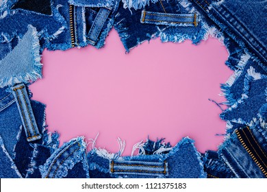 Denim frame from Lots of little ripped pieces of denim jeans fabric on pink leather background. Ripped Destroyed Torn Denim Frame, copy space