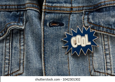 Denim jacket with cool graphic pin, funky metallic fashion accessory, artsy jeans garment badge