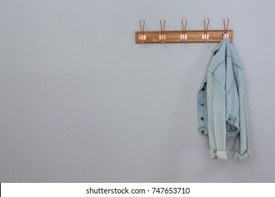 Denim jacket hanging on hook against wall
