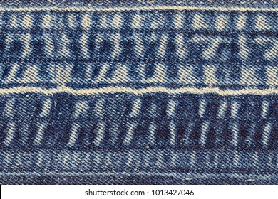 Denim jeans background. Ripped denim fabric with bleached scratch trace, text place, copy space.