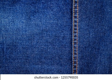 Denim jeans blue background and orange classic double denim seam, text place, copy space.