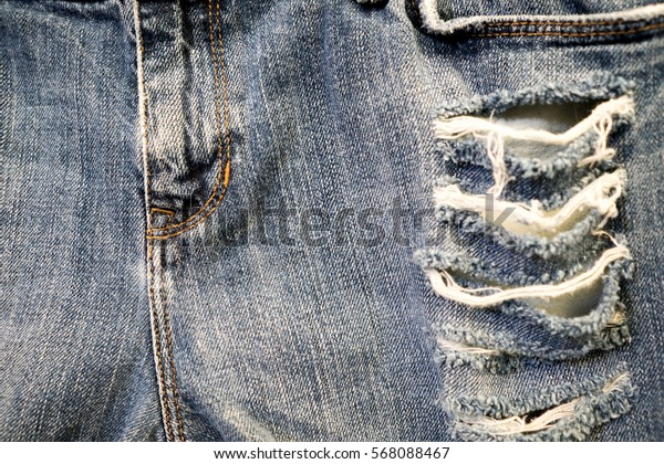 Denim jeans fabric texture background with old torn for design. torn blur denim.