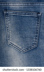 Denim pants (dark blue jeans) in close up detail with pocket, fabric texture background with copy space, flat lay