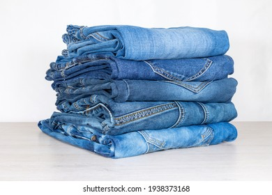 Denim trousers folded in a pile on a store window.