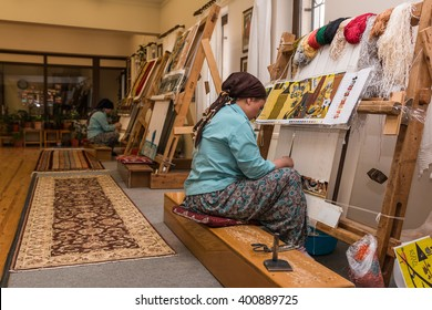 DENIZLY, TURKEY - MARCH 12th 2016: Turkish woman making wool a carpet on the cotton strings in the carpet workshop