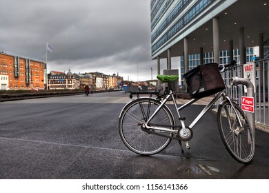 Denmark, Aarhus - October 18, 2014: Bicycle with a bag in the parking lot near a modern building in the city of Århus