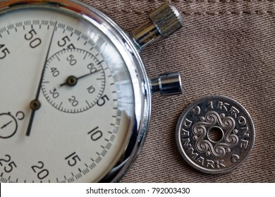 Denmark coin with a denomination of 1 krone (crown) and stopwatch on beige denim backdrop - business background