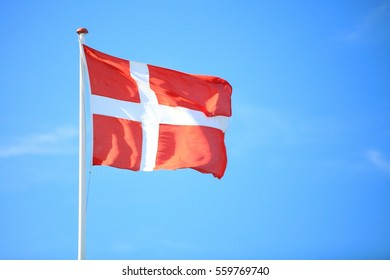 The denmark or danish flag with blue sky on background