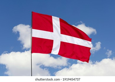 Denmark flag isolated on the blue sky with clipping path. close up waving flag of Denmark. flag symbols of Denmark.