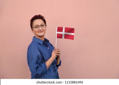 Denmark flag. Woman holding Danish flag. Nice portrait of middle aged lady 40 50 years old with a national flag over pink wall background outdoors.Learn Danish language. Visit Denmark concept.