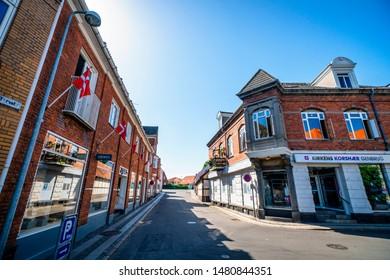 NEXØ, DENMARK - JUNE 30 - 2019: Danish flags in the streets of Nexø city in Denmark on the island Bornholm