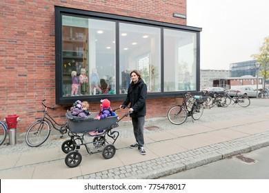 Denmark - October, 21. 2014: Man and children in a stroller near the windows of a kindergarten. Copenhagen