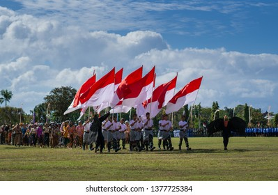 Denpasar, Bali / Indoesia - 17 August 2017: Group of people at the Indonesian independence parade, holding Indonesian flag, with couple of millitary and traditional people folloowing behind.