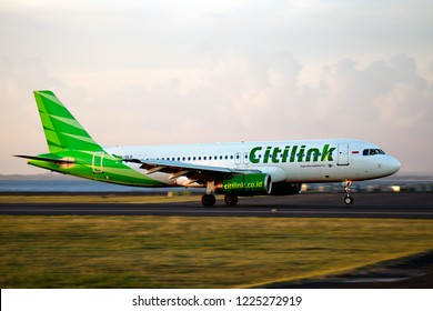 Denpasar, Bali / Indonesia - 03.23.2018. Ngurah Rai International Airport. Passenger aircraft Airbus A320 of Citilink Airlines landing during the sunset time.