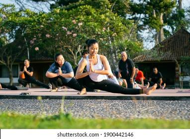 Denpasar, Bali, Indonesia - 19 September 2019: Yoga teacher do the yoga pose in a yoga group session retreat.