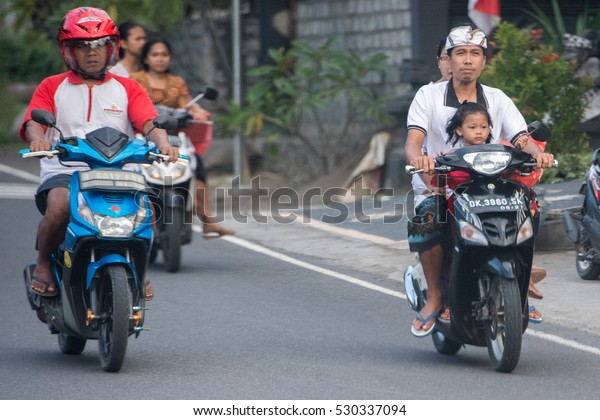 DENPASAR, BALI, INDONESIA - AUGUST 15, 2016 - Indonesia congested traffic, thousand of bikes with childrens and families are running without any rule on island small roads.