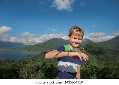 Denpasar, Bali/ Indonesia - June 15, 2016: Young boy stands on top of a  mountain and holds the iguana on his hand. Ubud area. Bali. Indonesia.