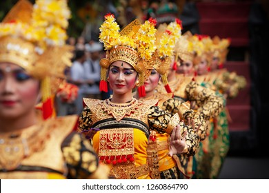 DENPASAR, BALI ISLAND, INDONESIA - JUNE 23, 2018: Face portrait of beautiful young Balinese women in ethnic dancer costume, dancing traditional temple dance Legong at art and culture festival parade.