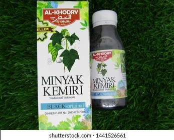 Denpasar, Indonesia - July 4 2019 : Close up view of Minyak kemiri or candlenut extract oil isolated on green grass background ready for sale. Indonesian traditional recipe. AL KHODRY BRAND BLACK