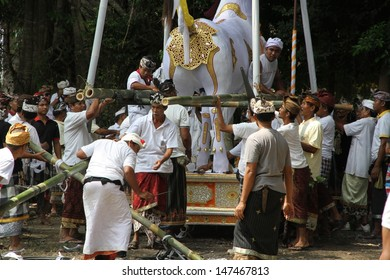 DENPASAR, INDONESIA - MAY 12: The villagers lifting the coffin on their shoulders at a Ngaben or cremation ceremony with spectators surrounding in Ubud, Denpasar, Bali, Indonesia on May 12, 2013.