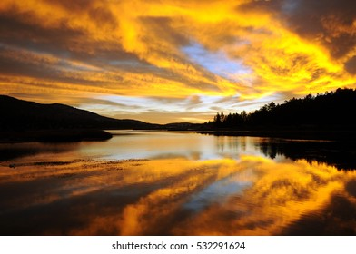 Dense golden sunrise reflects in mountain lake with silhouetted shoreline framing the scene.
