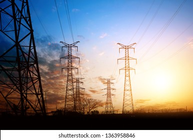 Dense high-voltage towers, the sky at dusk.