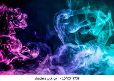 Dense multicolored smoke of   blue and pink colors on a black isolated background. Background of smoke vape
