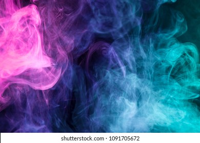 Dense multicolored smoke of pink,  blue and purple colors on a black isolated background. Background of smoke vape