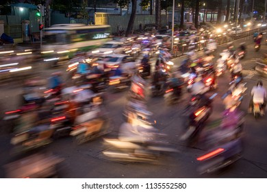 Dense traffic at night intersection with blurred lights passing through motorbikes and vehicles, Saigon, Vietnam.